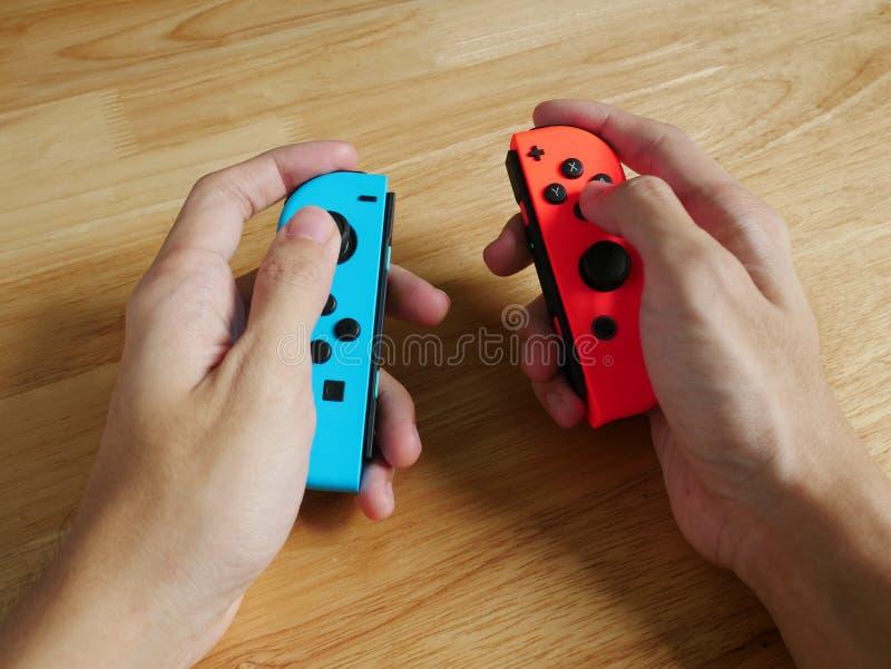 Nintendo-Schakelaarcontrolemechanismen in handen worden gehouden die royalty-vrije stock afbeeldingen