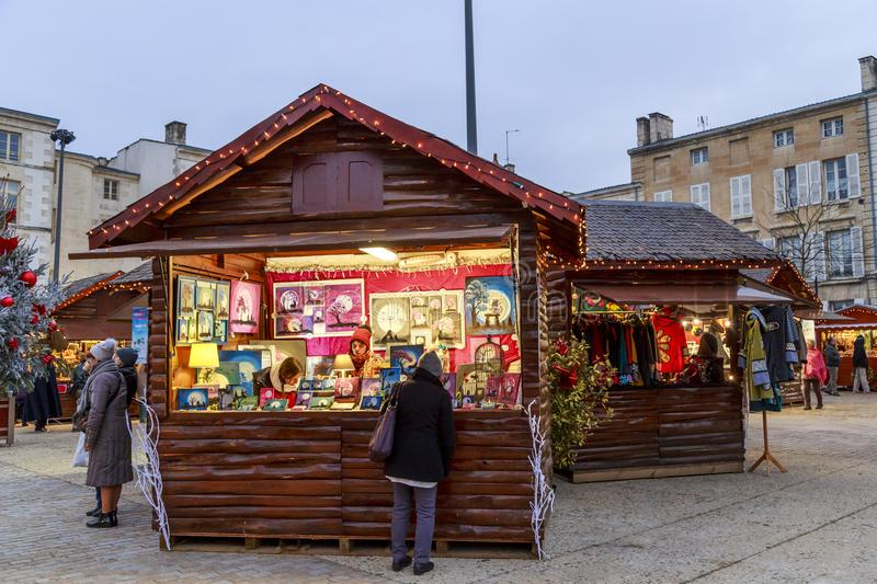 Christmas market at night during the festive period vendors sell from temporary wooden chalets. Niort, France - December 03, 2017: Christmas market at night stock image