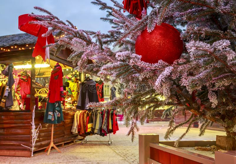 Close-up of a Christmas ball hanging on a snowy tree with Christmas market chalets in the backgr. Niort, France - December 05, 2017:Close-up of a Christmas ball royalty free stock photography