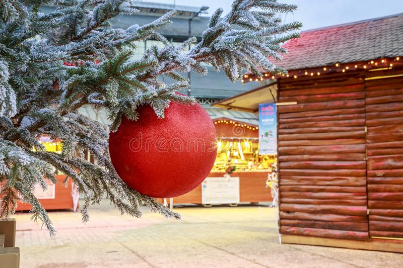 Close-up of a Christmas ball hanging on a snowy tree with Christmas market chalets in the backgr. Niort, France - December 05, 2017:Close-up of a Christmas ball stock photography