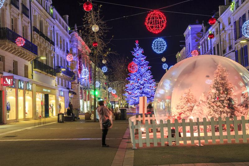Pedestrian street illuminated by Christmas decoration with a big glass ball in the foreground stock photos