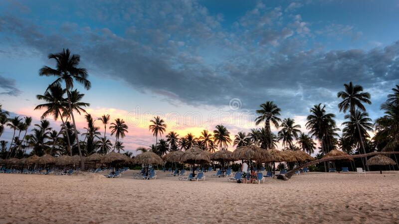 Nipa Hat Surrounded With Palm Trees Under White Clouds and Blue Skies Under Orange Sunset stock images