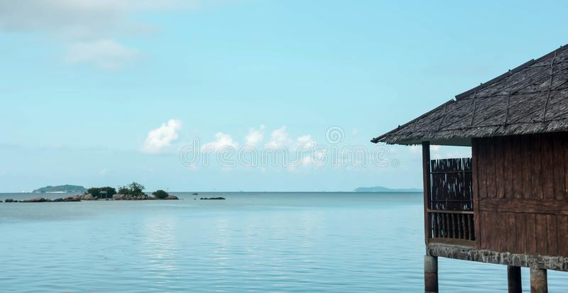 Nipa hut bungalow standing on a beach with ocean background. Nipa hut bungalow standing in a beach resort with ocean background and blue sky stock image