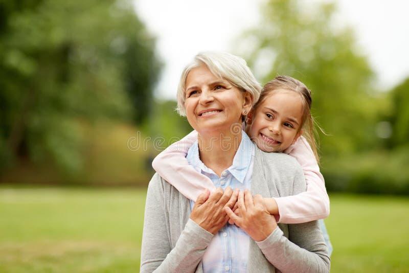 Nipote che abbraccia nonna al parco di estate fotografie stock