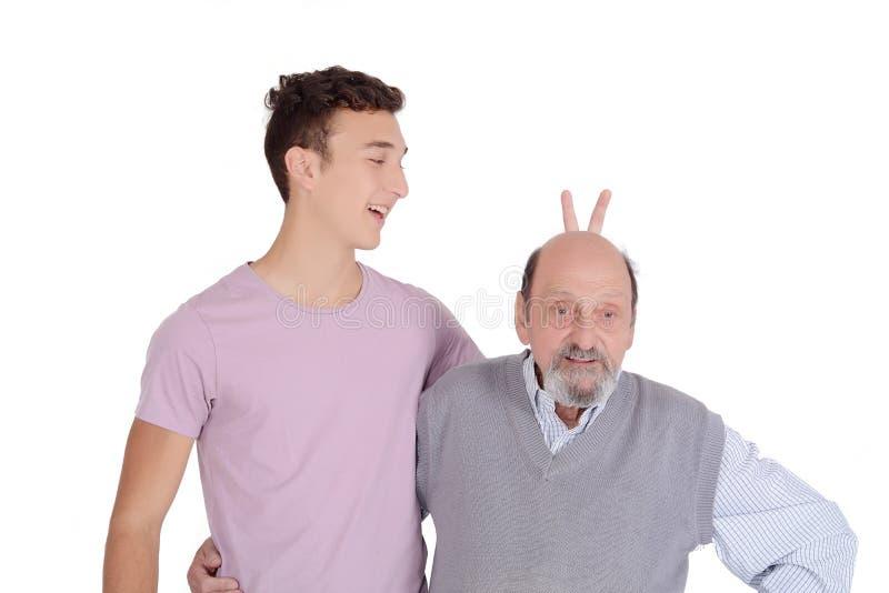 Nipote che scherza suo nonno con le orecchie del coniglietto fotografia stock