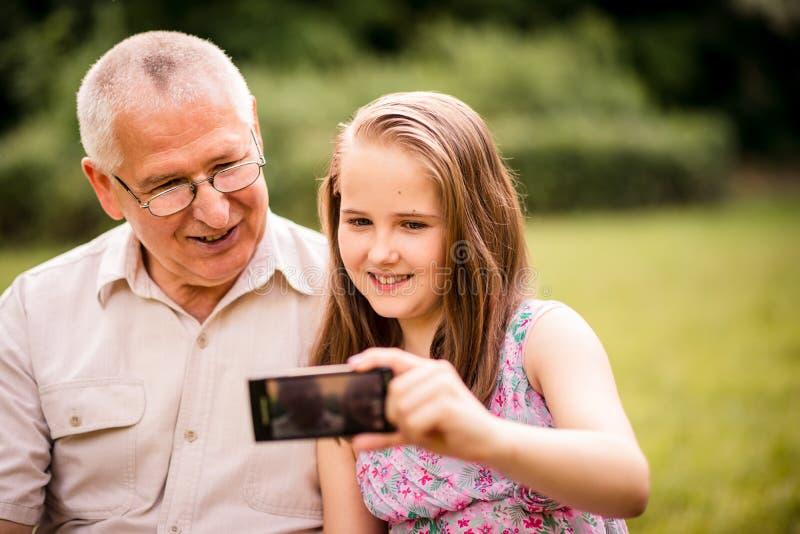Nipote con il nonno che cattura i momenti fotografia stock