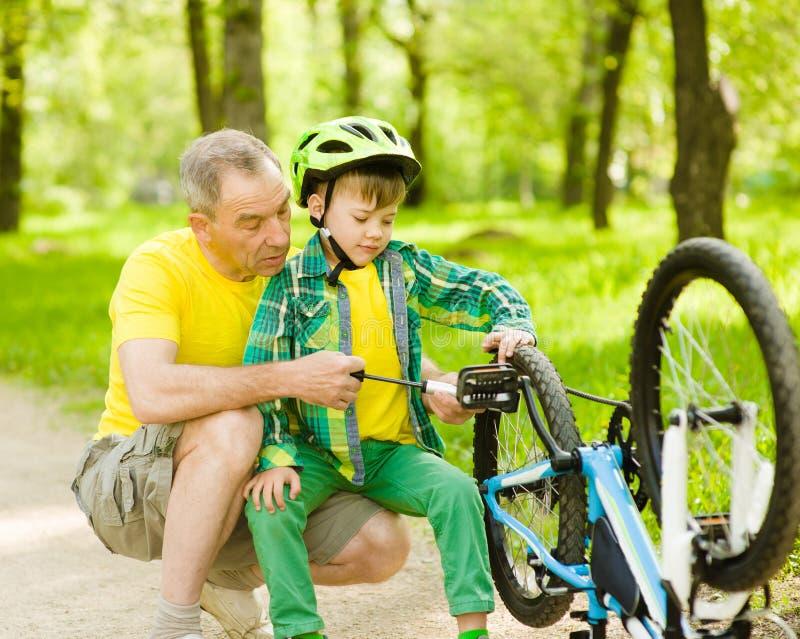 Nipote con la sua bicicletta della ruota pompata nonno immagine stock libera da diritti