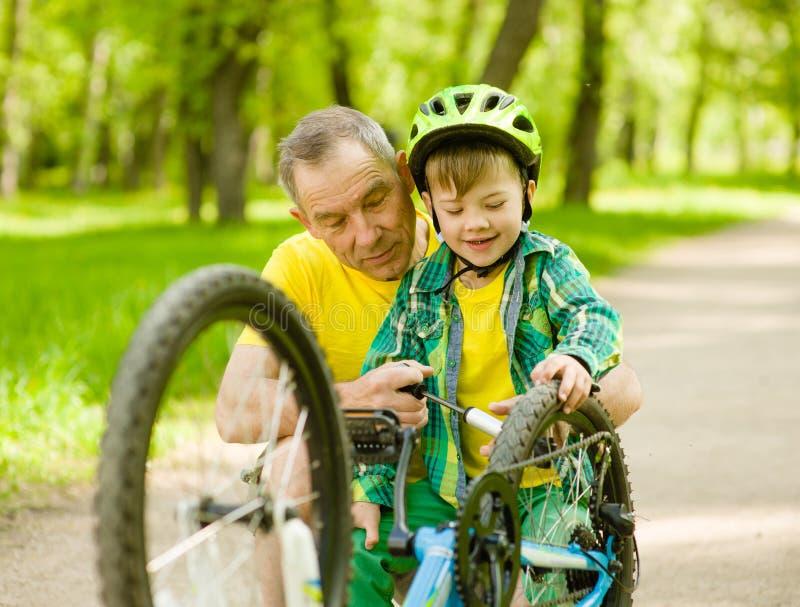 Nipote con la sua bicicletta della ruota pompata nonno fotografia stock libera da diritti