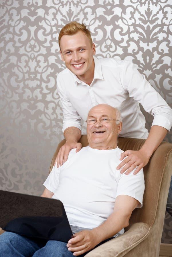 Download Nipote Dietro Suo Nonno Con Il Computer Portatile Fotografia Stock - Immagine di laptop, faccia: 55351544