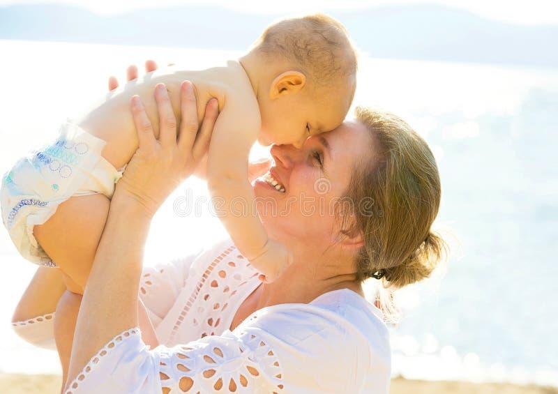 Nipote sorridente del bambino della nonna felice, fondo del lago isolato testa a testa, mare fotografia stock