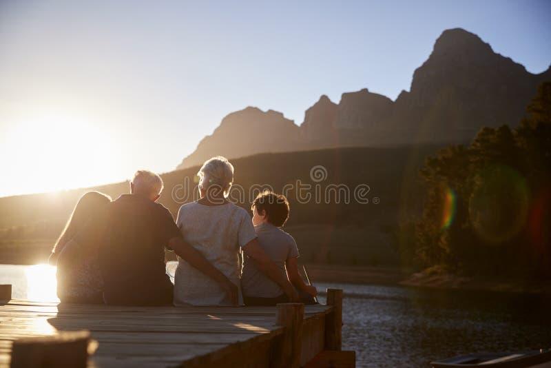Nipoti con i nonni che si siedono sul molo di legno dal lago immagini stock libere da diritti