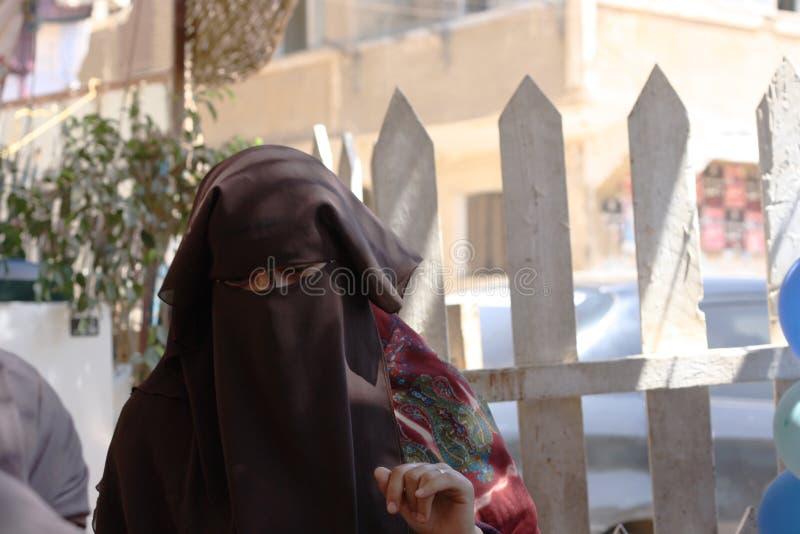 Niqabivrouw in spelgrond wordt versluierd met jonge geitjes dat stock afbeelding