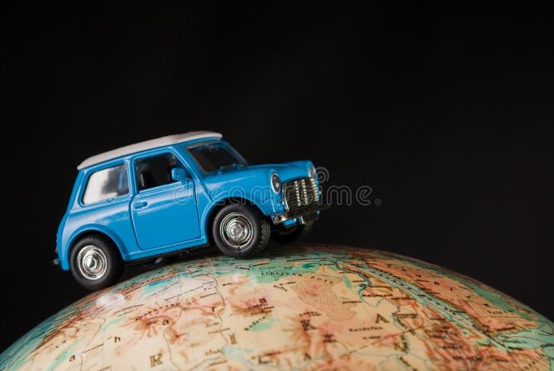 NIS, SÉRVIA - 8 de janeiro de 2018 figura diminuta carro Mini Morris do brinquedo no globo geográfico da terra no fundo preto no  imagem de stock