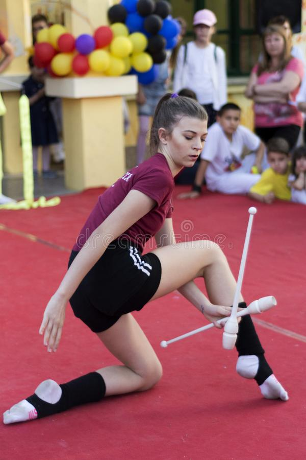 Young teen girl juggling with sticks on public stage royalty free stock photography