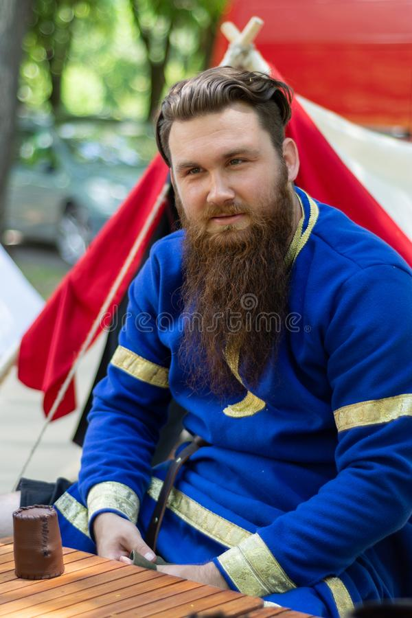 Portrait of a knight with a beard in a blue traditional suit sits royalty free stock photo