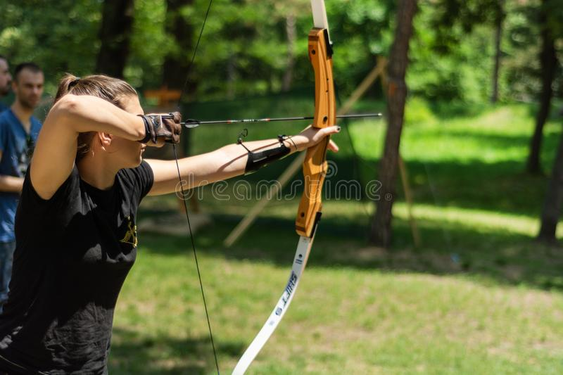 Professional girl archer with bow shoot arrow in the forest on knight festival and tournament. Nis, Serbia - June 16. 2019: Professional girl archer with bow stock photo