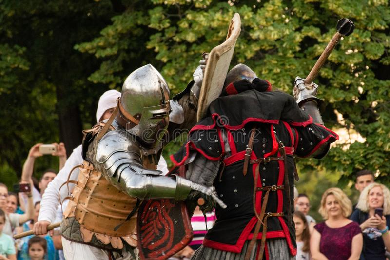 Two warrior knights with weapon and helmet fighting on the battlefield royalty free stock photo