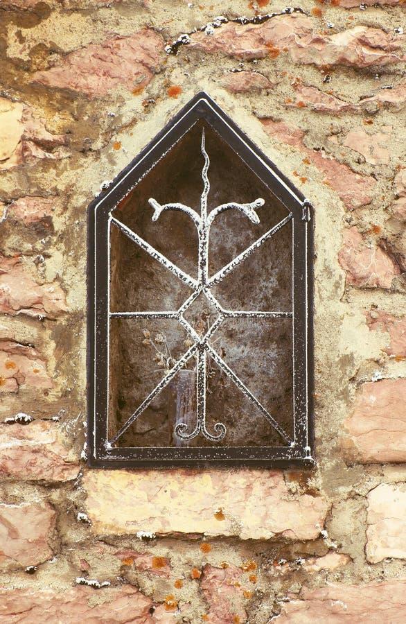Nische in der steinigen Wand des Dorfhauses mit gefrorener Blume Forged korrodierte Stahlstangen stockfotografie
