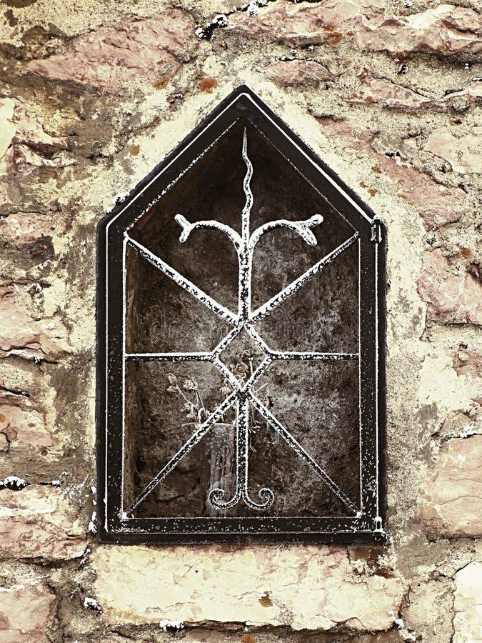 Nische in der steinigen Wand des Dorfhauses mit gefrorener Blume Forged korrodierte Stahlstangen lizenzfreie stockfotografie