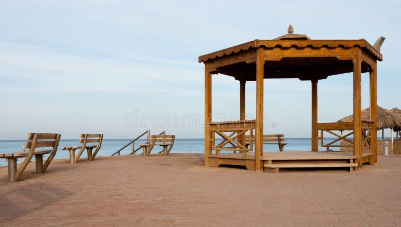 Nische und Bänke auf dem Strand Große hölzerne Nische und zwei Bänke auf Sand stützen unter Leerer Platz für das Treffen nahe Mee lizenzfreie stockbilder