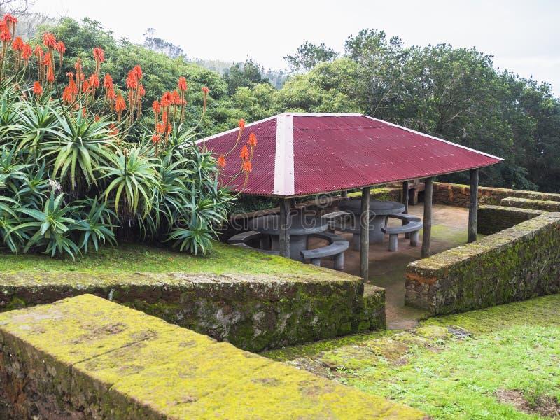 Nischenportal mit setzendem Blumengarten am Standpunkt an Maia-Dorf, Sao-Miguel-Insel, Azoren, Portugal, bewölkter Winter stockbilder