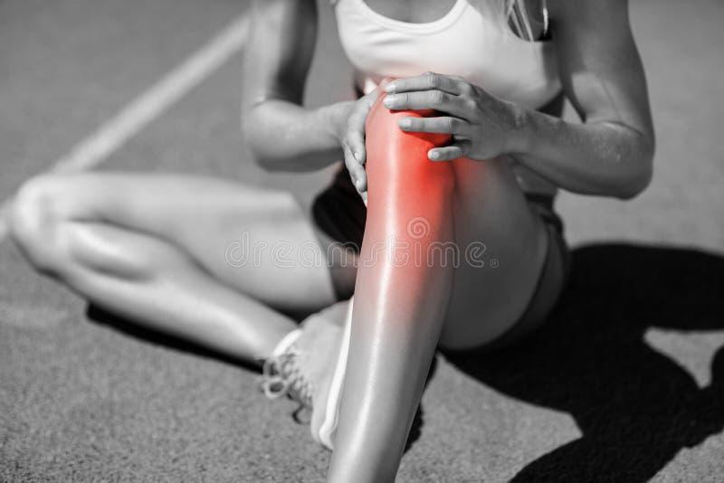 Niska sekcja żeńskiej atlety cierpienie od łącznego bólu zdjęcia stock