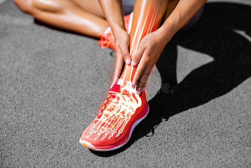 Niska sekcja żeńskiej atlety cierpienie od łącznego bólu na śladzie fotografia royalty free