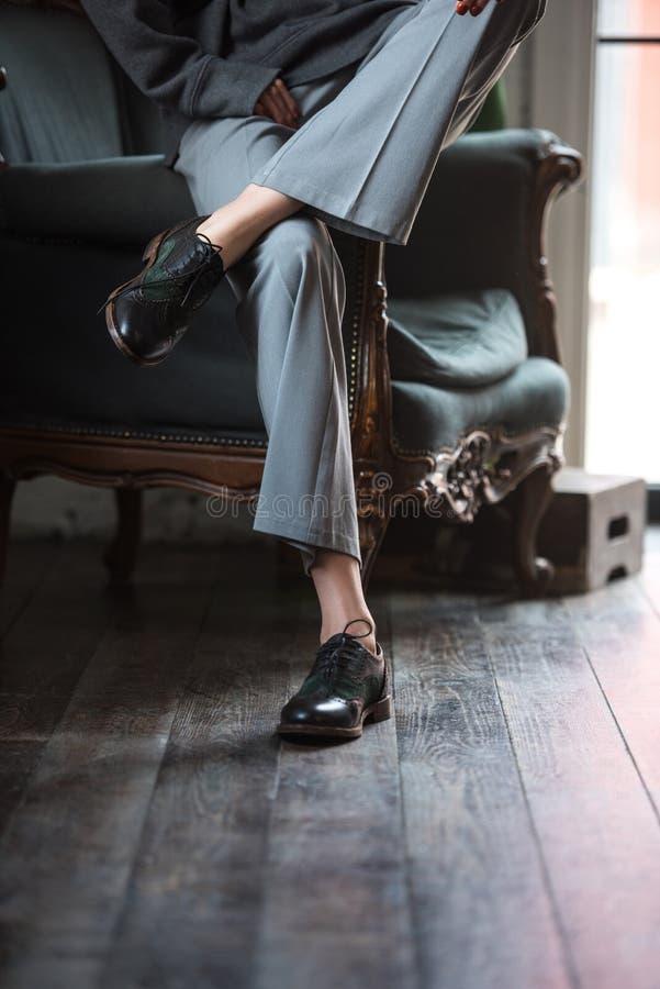 niska sekcja dziewczyna w rzemiennych butach i eleganckim spodń siedzieć obraz stock