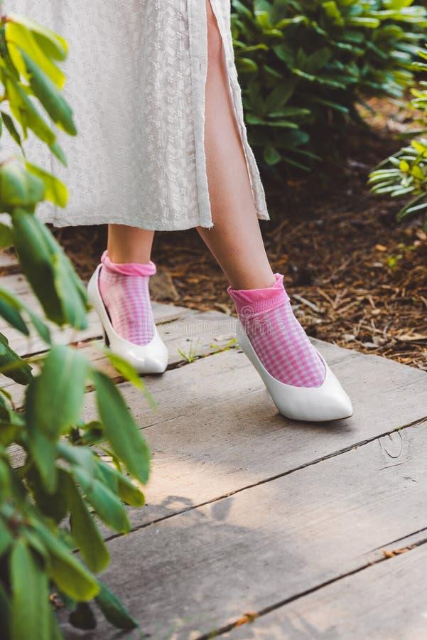 niska sekcja dziewczyna w smokingowy i elegancki biały butów chodzić zdjęcie stock