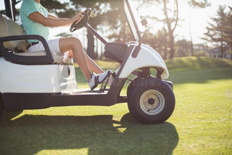 Niska sekcja golfisty mężczyzna jeżdżenia golfa powozik obraz royalty free