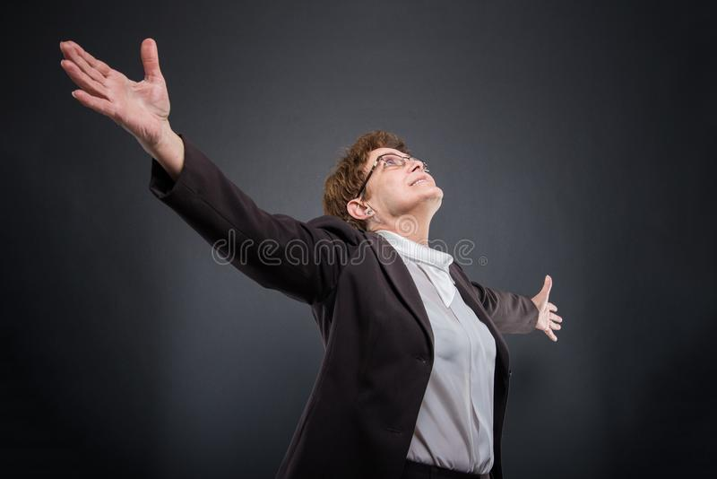 Niski kąt biznesowa starsza dama pozuje z rękami otwiera obraz royalty free