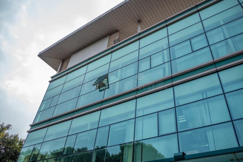 Niski kąt budynek biurowy z szklaną powierzchownością na chmury nieba tle obrazy stock
