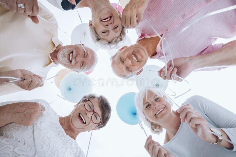 Niski kąt szczęśliwi starsi ludzie w okręgu z balonami zdjęcia royalty free
