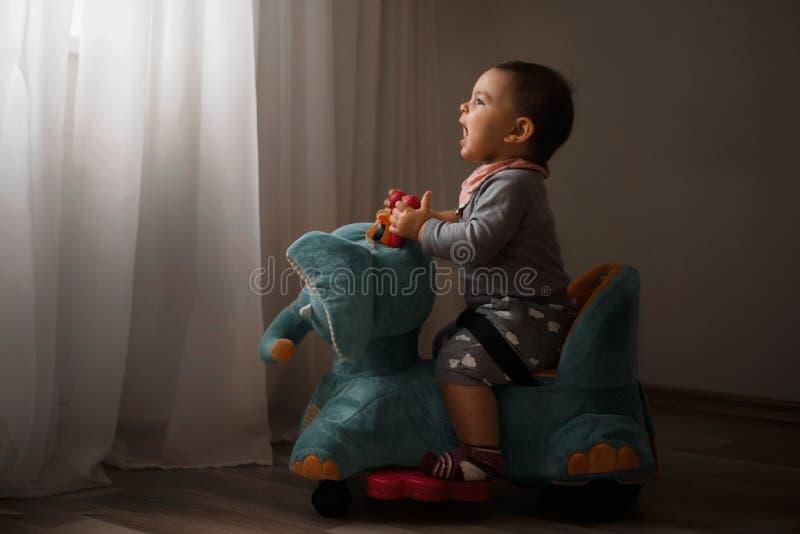 Niskiego światła fotografia bawić się indoors w domu na słoń zabawki szczęśliwych wspominkach todler dziecko obrazy royalty free