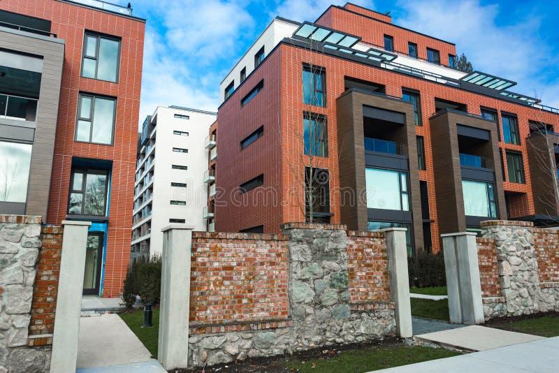 Niskiego kąta widok na nowożytnej mieszkaniowej ceglanej budynek mieszkaniowy powierzchowności z wielkimi okno Nowożytny kompleks fotografia royalty free