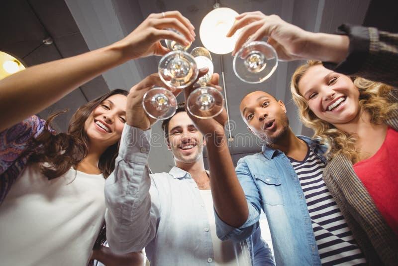 Niskiego kąta portret szczęśliwi koledzy wznosi toast z szampanem w biurze obrazy stock