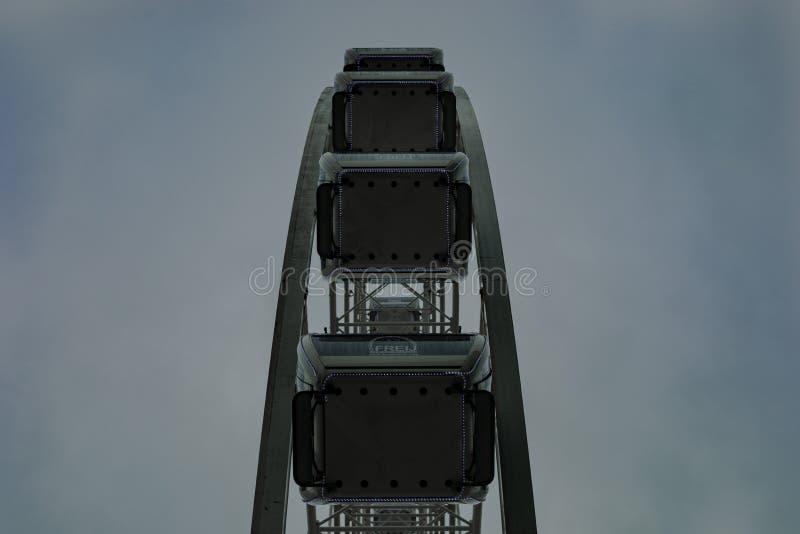 Niskiego kąta symmetric strzał pusty Ferris koło z ciemnym chmurnym popielatym tłem zdjęcie royalty free