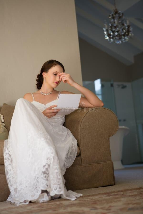 Niskiego kąta widok czyta ślubną kartę piękna panna młoda podczas gdy siedzący na kanapie zdjęcie royalty free