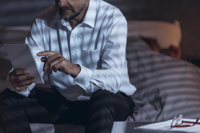 Niskiego kąta widok dojrzały męski obsiadanie na łóżku w h i pokoju fotografia royalty free