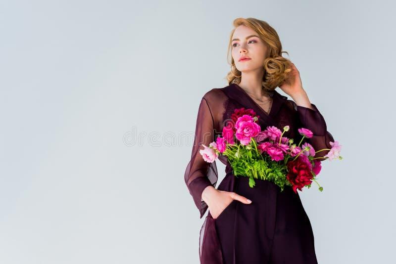 niskiego kąta widok elegancka młoda kobieta patrzeje daleko od z pięknymi kwiatami obrazy royalty free