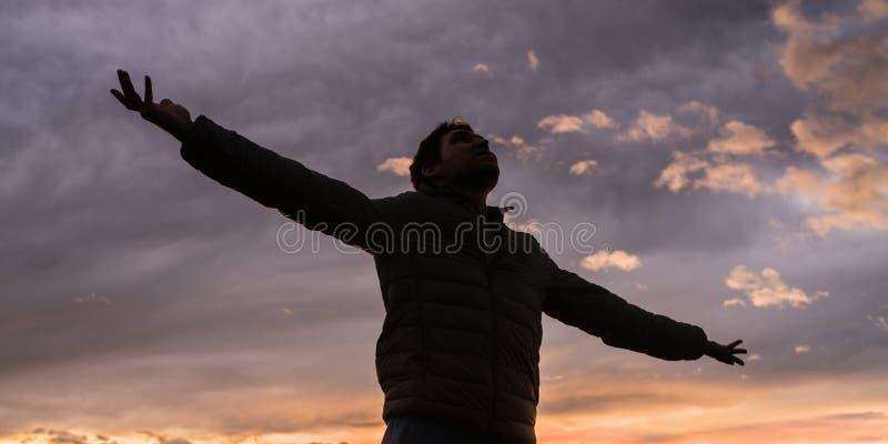 Niskiego kąta widok młody człowiek pozycja pod rozjarzonym wieczór niebem obraz stock