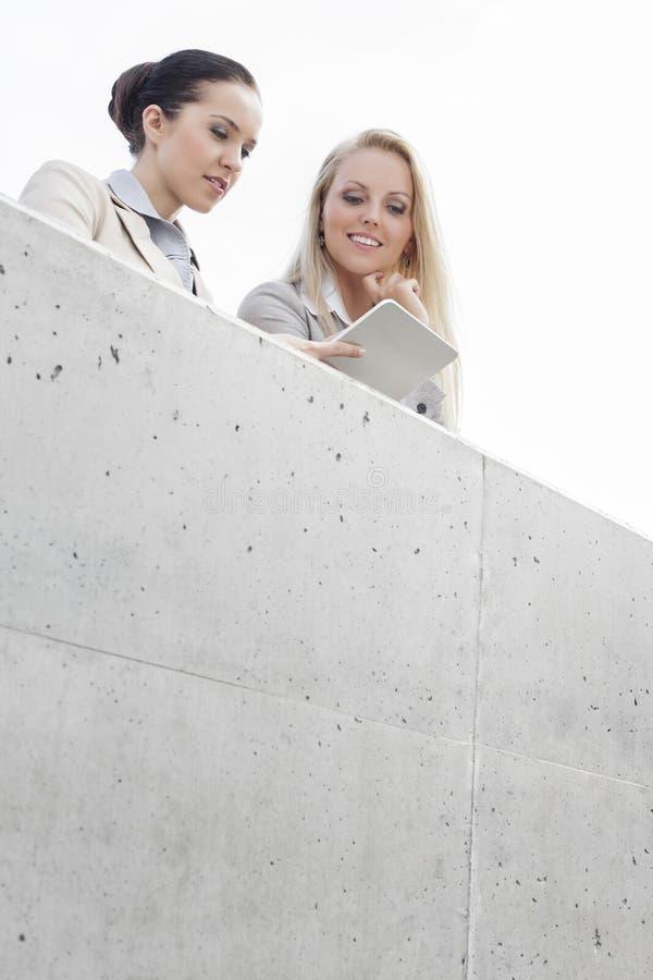 Niskiego kąta widok młodzi żeńscy dyrektory wykonawczy używa cyfrową pastylkę podczas gdy stojący na tarasie przeciw niebu zdjęcie stock