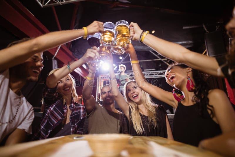 Niskiego kąta widok szczęśliwi przyjaciele wznosi toast piwnych szkła podczas gdy siedzący przy stołem obrazy royalty free