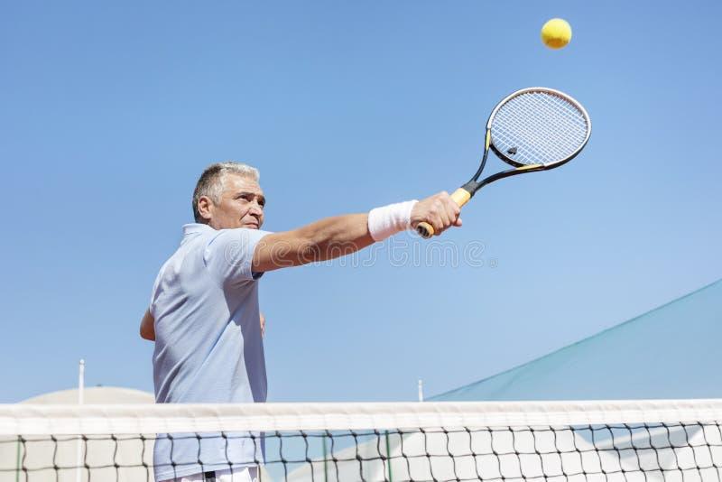 Niskiego kąta widok ufny dorośleć mężczyzny uderza tenisową piłkę z kantem na sądzie przeciw jasnemu niebieskiemu niebu zdjęcie royalty free
