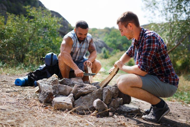 Niskiego kąta zakończenie up dwa młodego męskiego turysty w drewnie, organizować obozuje ogień dla grilla Pomagać Each Inny zdjęcie stock