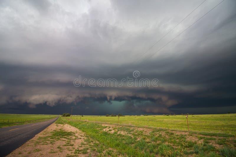 Niskiej półki obłoczna i potężna supercell burzy pełnia niebo nad wiejską drogą fotografia royalty free