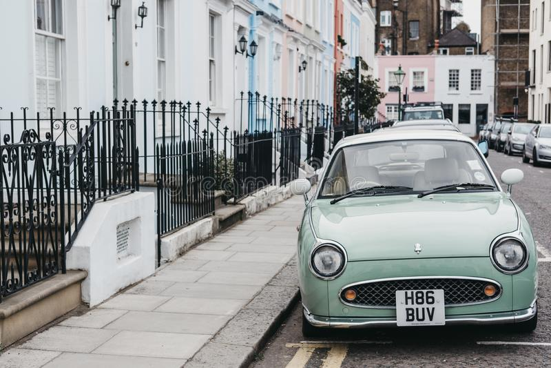 Nissan Figaro blu pastello accanto alle case pastelli in Notting Hill, Londra immagine stock