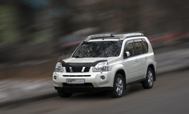 Nissan white car. Nissan white car on blurred in motion background royalty free stock photos