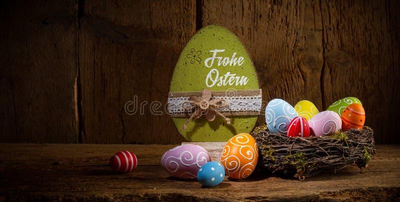 Nisten glückliche bunte gemalte Eier Ostern deutscher Übersetzung Grüße Frohe Ostern englischer in den Vögeln Korb auf rustikalem lizenzfreies stockbild