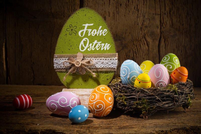 Nisten glückliche bunte gemalte Eier Ostern deutscher Übersetzung Grüße Frohe Ostern englischer in den Vögeln Korb auf rustikalem stockfotos